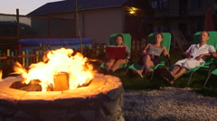 People relaxing in back yard sitting on patio loungers near fire pit at dusk Arkistovideo