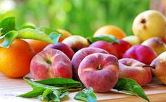 Ripe peaches and pears, oranges, on table Stock Photos