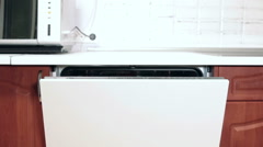 White facade of opened cover of built-in dishwasher machine at the kitchen Stock Footage