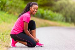African american woman runner tightening shoe lace - Fitness, people and heal - stock photo