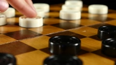 Two persons start playing on checker board, slow motion, close up Stock Footage