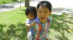 Brother holding his sister on his back in garden Stock Footage