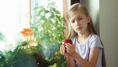 Child has a toothache. Girl really wants to eating a apple but can not - stock footage