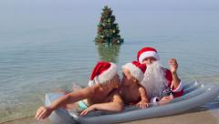 Family enjoying tropical beach holiday near Christmas tree in surf greeting Stock Footage
