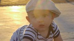 Little baby wearing hat crawling outdoor at sunset Stock Footage