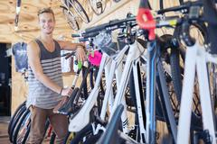 Portrait smiling young man leaning on rack in bicycle shop Stock Photos