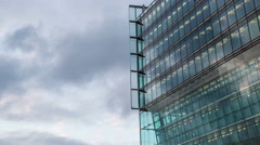 Cloudy sky with modern illuminated reflected glass  facade timelapse Stock Footage