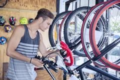 Young man examining bicycle on rack in bicycle shop - stock photo