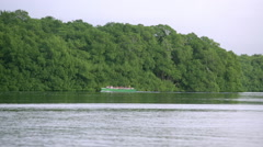People in boat ride pass river Stock Footage