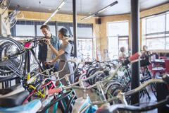Stock Photo of Couple browsing bicycles on rack in bicycle shop