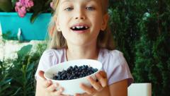 Girl sniffing and showing bowl with blueberries at camera. Closeup Stock Footage