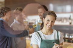 Portrait smiling worker with clipboard in winery tasting room Stock Photos