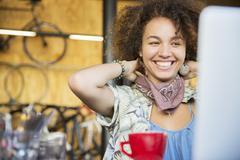 Smiling woman at laptop in bike shop adjusting neck scarf Stock Photos