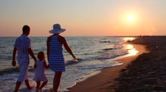 Family on beach getaway walking away holding hands along surf line at sunset - stock footage