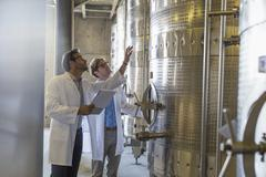 Vintners in lab coats checking vats in winery cellar Stock Photos