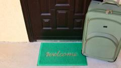 Welcome home door mat with suitcase travel background Stock Footage