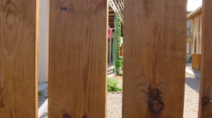Looking through a wooden picket fence around backyard of residential building - stock footage