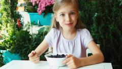 Girl eating very tasty blueberries with sugar.  Child resting Stock Footage