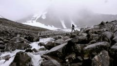 1067 man walking over a bridge in kebnekaise Stock Footage