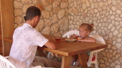 Father with her daughter have breakfast in outdoor summer kitchen Stock Footage