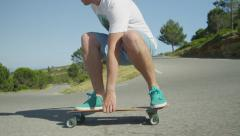 SLOW MOTION: Young man longboarding down the winding road Stock Footage