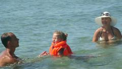 Young family on beach vacation have fun in water teaching daughter how to swim Stock Footage