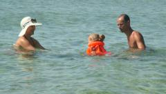 Family on beach vacation teaching little daughter in inflatable vest how to swim Stock Footage