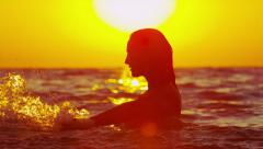 SLOW MOTION: Cheerful woman splashing and playing in the sea - stock footage