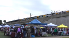 Weekend outdoor  clothing market  by train station Stock Footage