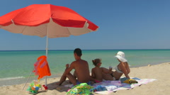 Family on sand beach in shade of red umbrella against turquoise sea and blue sky Stock Footage