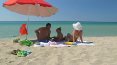 Family on sand beach in shade of umbrella against turquoise water and clear sky Stock Footage