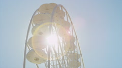 CLOSE UP: Sun shinning through spinning ferris wheel Stock Footage