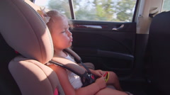 Little girl traveling with family by car singing road trip song - stock footage