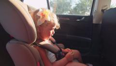 Pretty little girl sings song sitting in child back seat of car on trip Stock Footage