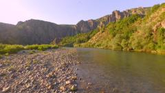 Stock Video Footage of Beautiful River Bank Close Up Areal Water Flowing Rocks Trees Cliffs Stone