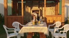 Dining table served in the patio area for family dinner beside stone fireplace Stock Footage