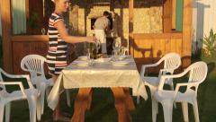 Young family serving dining table in garden near outdoor stone fireplace Stock Footage
