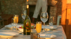 Dining table served simple food in backyard beside outdoor stone fireplace Stock Footage