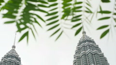 Stock Video Footage of Petronas Twin Towers is surrounded by trees, captured during daytime.