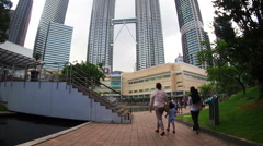 Tourist taking a walk at a nearby park at Petronas Twin Tower Stock Footage