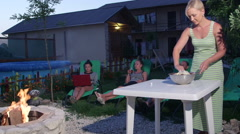 Friends relaxing on lounge chairs in garden around stone fire pit in evening Stock Footage