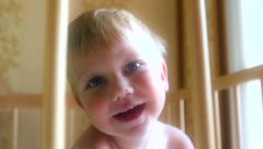 Kid baby child boy toddler is smiling in a cot Arkistovideo
