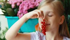 Girl sniffing and showing a bunch of red currants. Girl playing with currant. Stock Footage