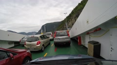 Passengers, cars, buses ride the ferry which transports them in Fjords Stock Footage