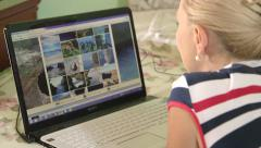 Woman in search of summer vacation offers browsing travel sites using laptop Stock Footage