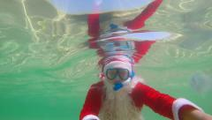 Santa Claus diver on tropical beach vacation snorkeling in turquoise water Stock Footage