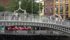 People walk across the Ha'penny Bridge, Dublin, Ireland Stock Footage