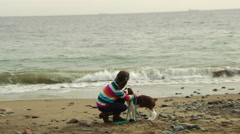 A young girl hugging her dog on the beach - stock footage