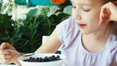 Girl eating blueberries with sugar. Child sitting resting on the table Stock Footage