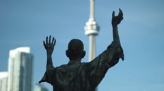 Statue worshipping CN tower Stock Footage
